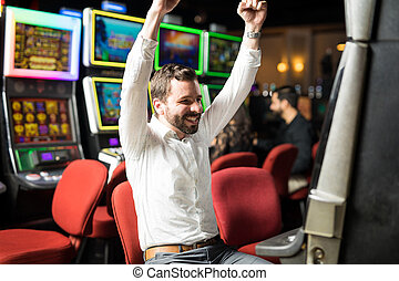 Excited man winning in a slot machine