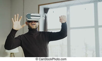 Excited man with virtual reality headset playing 360 video...