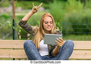 excited metal lover watching something on her tablet