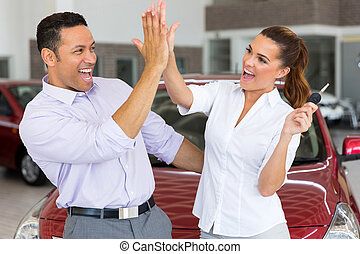 mid age couple giving high five after buying new car
