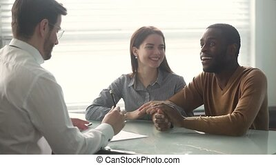 Excited mixed ethnicity couple sign loan contract handshake...