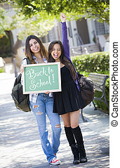 Excited Mixed Race Female Students Holding Chalkboard With Back To School Written on it.