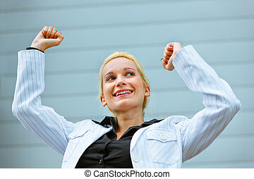 Excited modern business woman standing at office building...