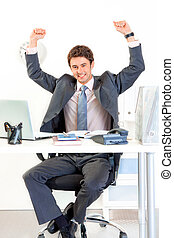 Excited modern businessman sitting at office desk and...