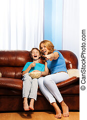 Excited mother pointing at TV with laughing son
