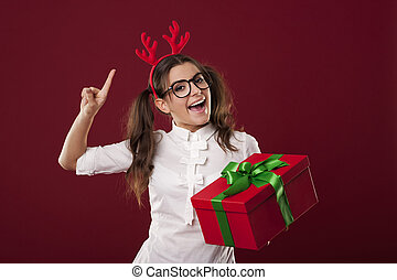 Excited nerdy woman with red christmas present