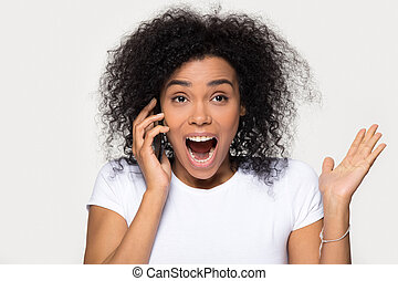 Excited overjoyed african girl hearing great news talking on phone