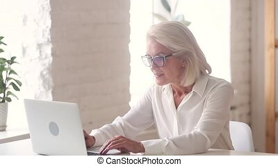 Excited overjoyed old businesswoman looking on laptop...