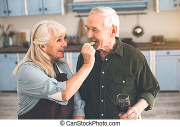 Excited pensioners tasting healthy vegetable in cook room
