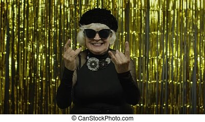 Excited positive senior old woman showing rock and roll gesture and sincerely smiling, lady enjoying on concert, activity. Elderly stylish grandma showing tongue on golden background. 6k slow motion