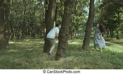 Excited pregnant couple playing catch-up in park