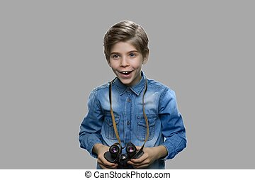 Excited preteen boy using binoculars.