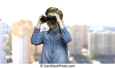Excited preteen boy using binoculars. Curious caucasian...