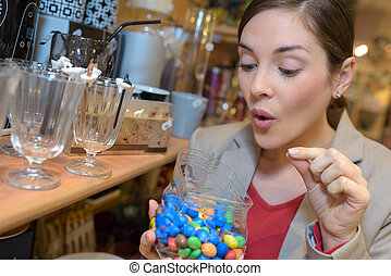 excited pretty woman picking candies in store