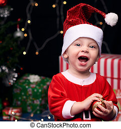 Excited Santa baby laughing while hilding christmas...