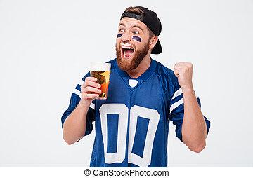 Excited screaming man fan drinking beer make winner gesture.