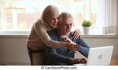 Excited senior couple winners using laptop overjoyed by...