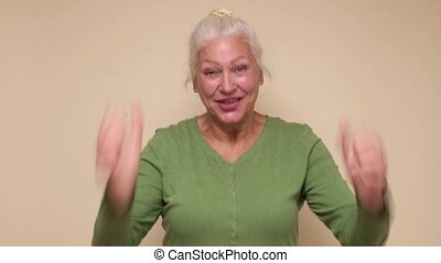 Excited senior woman screaming laughing make fists gesture Yes, getting what she wants succeed. Grandmother reached a goal, celebrating victory