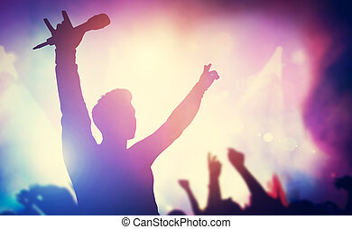 Excited singer raising hands on stage. Concert, musical gig...