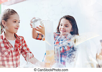 Excited smart girls mixing liquids during chemistry lesson at school