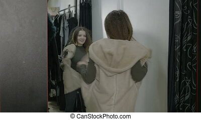 Excited smiling business woman shopping trying jackets in...
