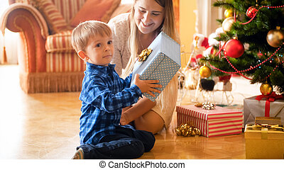 Excited smiling little boy holding big box with Christmas gift