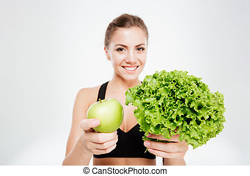Excited smiling sports woman showing lettuce and green apple...