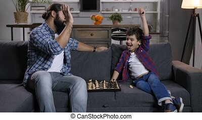 Excited son defeated joyful father in chess game