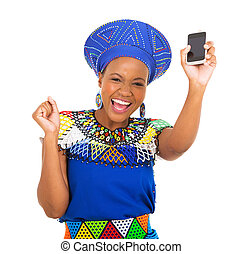 excited south african woman holding mobile phone