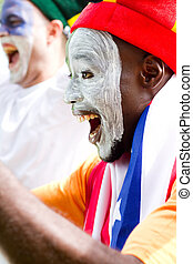 excited sports fans cheering excitedly with painted faces...