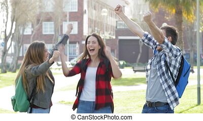 Three excited students jumping celebrating good news in a park