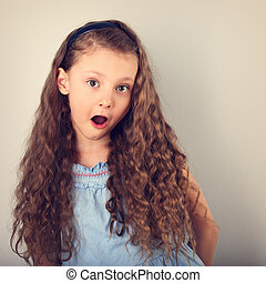 Excited surprising kid girl with long curly hair style and...