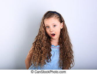 Excited surprising kid girl with wide open mouth and big...