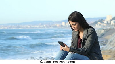 Excited teen reading good news on the beach - Excited teen...