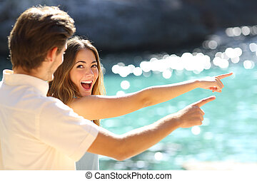 Excited teens pointing beach on vacation