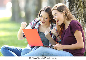 Excited teens receiving good news on line