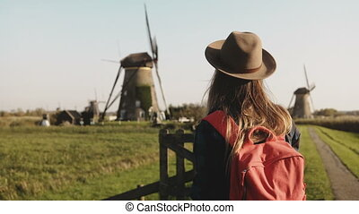 Excited tourist woman waves arms near a windmill. Traveler girl in hat with red backpack enjoys rustic mill scenery. 4K.