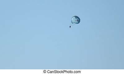 Excited tourists parasailing high in the sky extreme sport...