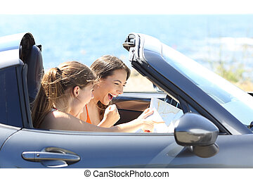 Excited tourists reading a map in a car on vacation