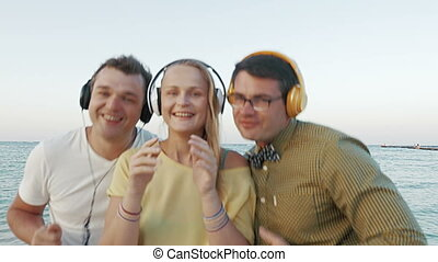 Excited trio enjoying music in headphones outdoor