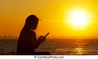 Excited woman at sunset checking phone news - Silhouette of...