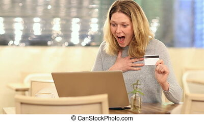 Excited woman buying online in a coffee shop