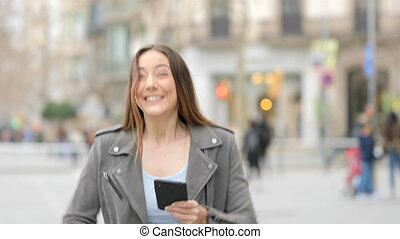 Excited young woman celebrating success checks phone in the street