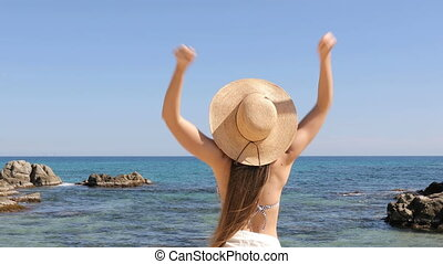 Excited woman celebrating vacation on the beach