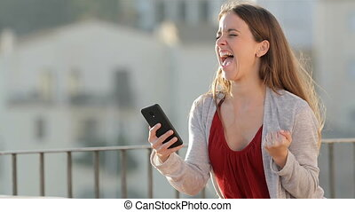 Excited woman checking mobile phone in a balcony