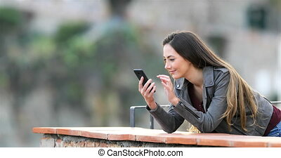 Excited woman checking phone content in a balcony - Excited...