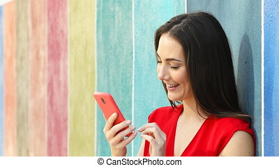 Excited woman checking phone in a colorful wall - Excited...