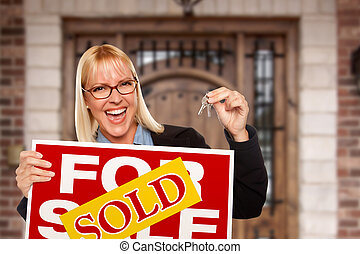 Excited Woman Holding House Keys and Sold Real Estate Sign in Front of Nice New Home