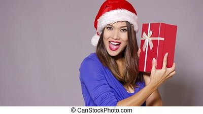 Excited woman in a Santa hat holding a gift