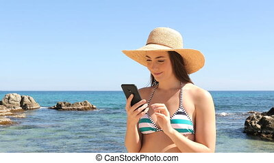 Excited woman in bikini reading good news on phone - Excited...
